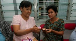 Woman shows another woman oral contraceptives in a clinic in Myanmar